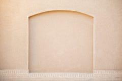 Alte beige Stuckwand mit verziertem Bogen Stockbilder