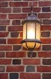 Alte beleuchtete Lampe auf alter verwitterter Backsteinmauer Stockfotografie