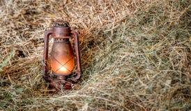 Alte beleuchtete Lampe im Heu Stockbilder
