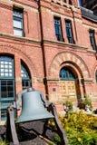Alte Bell durch Backsteinbau Stockfoto