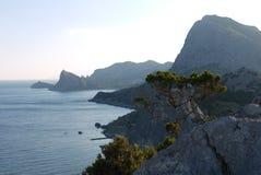 Alte, belle montagne sulla riva di un Mar Nero profondo Immagini Stock