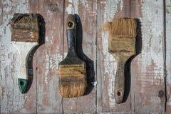 Alte benutzte Bürsten vor dem hintergrund einer alten getrockneten Farbe Lizenzfreie Stockfotografie