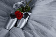 Alte benutzte Ballettpantoffel, die auf Boden mit den Rosafarbenen und Ballettröckchen artis liegen Stockfotografie