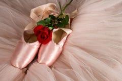 Alte benutzte Ballettpantoffel, die auf Boden mit Rosafarbenem und Ballettröckchen liegen Lizenzfreie Stockfotos