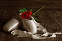 Alte benutzte Ballettpantoffel, die auf Boden mit Rosafarbenem und dem Blumenblatt liegen Stockfoto