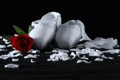 Alte benutzte Ballettpantoffel, die auf Bodenrot-Rose künstlerischem conver liegen Stockfotografie