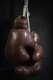 Alte benutzte Boxhandschuhe, hängend vor einer schmutzigen Wand Stockbild