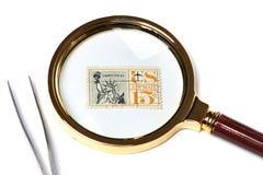 Alte benutzte Briefmarke und Vergrößerungsglas Stockbild