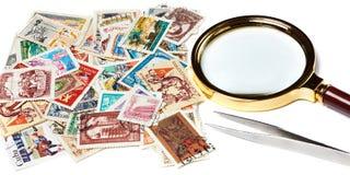 Alte benutzte Briefmarken und Vergrößerungsglas Lizenzfreies Stockfoto