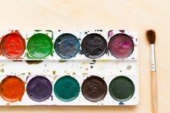 Alte benutzte Farben auf einem hölzernen Hintergrund Lizenzfreies Stockbild