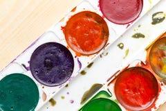 Alte benutzte Farben auf einem hölzernen Hintergrund Lizenzfreies Stockfoto