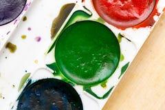 Alte benutzte Farben auf einem hölzernen Hintergrund Stockbilder