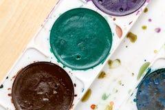 Alte benutzte Farben auf einem hölzernen Hintergrund Lizenzfreie Stockfotos