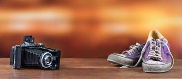 Alte benutzte purpurrote Turnschuhe mit alter Kamera Stockfotos