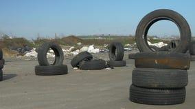 Alte benutzte Reifen werden auf der gepflasterten Straße gestapelt Viel Rückstand im Hintergrund Wind bewegt die Stücke des Abfal stock video footage