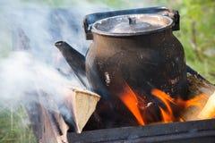 Alte benutzte schwarze kochende Teekanne auf Feuer Lizenzfreies Stockbild