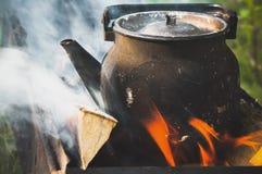 Alte benutzte schwarze kochende Teekanne auf Feuer Lizenzfreie Stockbilder