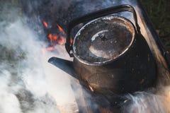 Alte benutzte schwarze Teekanne mit kochendem Wasser Stockfotografie