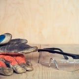 Alte benutzte Sicherheitsgläser und Handschuhe auf hölzernem Hintergrund Stockbilder