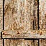 Alte benutzte und rostige Eisennägel auf einer Holztür Stockbilder