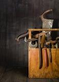 Alte benutzte Werkzeuge im Werkzeugkasten Dunkler Hintergrund Stellen-Beleuchtung Getrennter hölzerner Kasten Lizenzfreies Stockbild