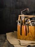 Alte benutzte Werkzeuge im Werkzeugkasten Dunkler Hintergrund Stellen-Beleuchtung Getrennter hölzerner Kasten Stockfotografie