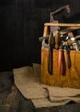 Alte benutzte Werkzeuge im Werkzeugkasten Dunkler Hintergrund Stellen-Beleuchtung Getrennter hölzerner Kasten Lizenzfreie Stockfotos