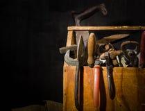 Alte benutzte Werkzeuge im Werkzeugkasten Dunkler Hintergrund Stellen-Beleuchtung Getrennter hölzerner Kasten Stockbilder