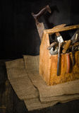 Alte benutzte Werkzeuge im Werkzeugkasten Dunkler Hintergrund Stellen-Beleuchtung Getrennter hölzerner Kasten Lizenzfreies Stockfoto