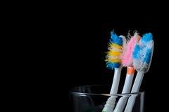 Alte benutzte Zahnbürsten im Glas auf schwarzem Hintergrund Lizenzfreie Stockfotografie