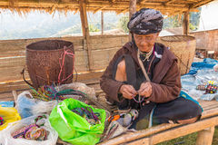 Alte Bergvolkfrau stellen ein Handwerksarmband her Stockfotografie