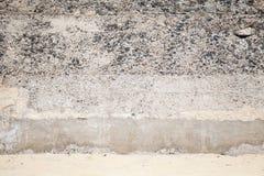 Alte Betonmauer mit Steinen und Sand Lizenzfreies Stockfoto