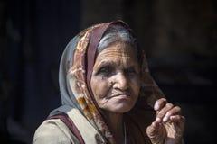 Alte Bettlerfrau auf Straße bei Dashashwamedh Ghat in Varanasi, Uttar Pradesh, Indien Stockbild