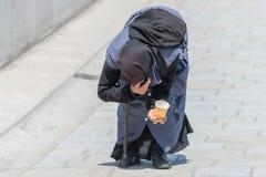 Alte Bettlerfrau verbog vorbei in eine Fußgängerzone, Deutschland Lizenzfreies Stockfoto