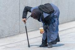 Alte Bettlerfrau verbog vorbei in eine Fußgängerzone, Deutschland Stockfotos