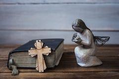 Alte Bibel und Kreuz des Engels auf hölzernem Hintergrund Lizenzfreie Stockbilder