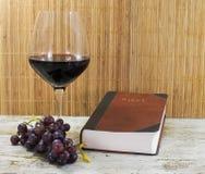 Alte Bibel und Rotwein mit Trauben Stockfoto