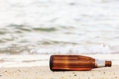 Alte Bierflasche auf Strand Stockfotos