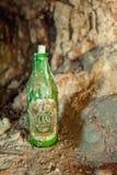Alte Bierflasche mit einer Kerze im Spitzenbratenfett mit Wachs lizenzfreie stockfotos