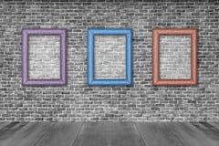 Alte Bilderrahmen auf Backsteinmauer Stockbilder