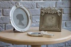 Alte Bilderrahmen, Lügenspiegel auf dem Tisch mit grauem Backsteinmauerhintergrund, Nahaufnahme Lizenzfreie Stockbilder