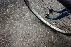 Alte blaue Fahrradfelge auf Straßenasphalt, -hintergrund und -beschaffenheit Stockbild
