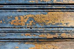 Alte blaue gebrochene Farbe auf einem orange hölzernen Türhintergrund Lizenzfreies Stockfoto
