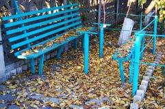 Alte blaue Holzbank und gefallener Herbstlaub Stockfotos