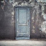 Alte blaue Holztür in der Betonmauer Stockfotos