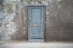 Alte blaue Holztür in der dunklen Betonmauer Lizenzfreie Stockbilder