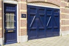 Alte blaue Holztür an Hausnummer 73 Stockfoto