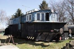 Alte blaue Lokomotive, die auf den Schienen auf dem Hintergrund des blauen Himmels steht Stockbild