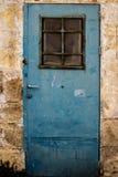 Alte blaue Metall-Schmutztür mit Fenster und rostigen Metall-lockas ein schöner Weinlesehintergrund Lizenzfreies Stockfoto