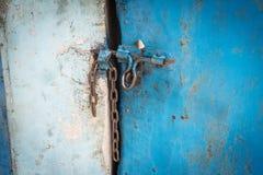 Alte blaue Stahltür schloss durch eine Kette Stockfotografie
